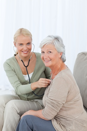 Nurse taking the heartbreat of her patient at home Stock Photo - 10175475