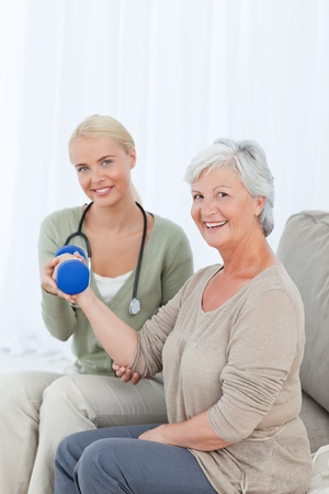 Beautiful nurse helping her patient to do exercises Stock Photo - 10174021