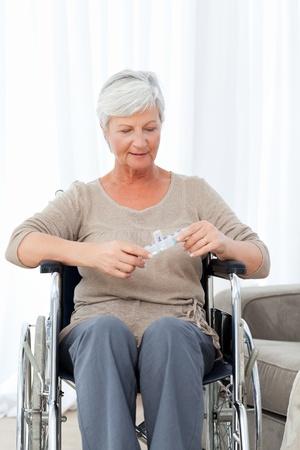 Senior in wheelchair with pills Stock Photo - 10175538