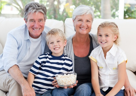 family line: Happy grandparents with their grandchildren looking at the camera Stock Photo