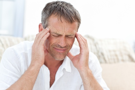 Hombre tener un dolor de cabeza en casa