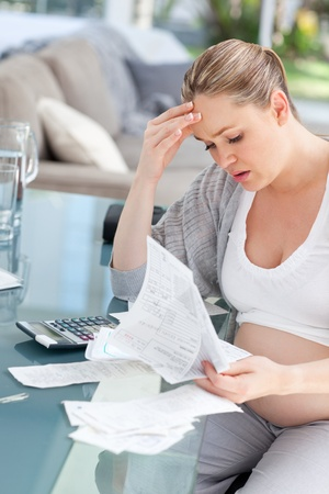 Worried pregnant woman calculating her domestic bills at home Stock Photo - 10171783
