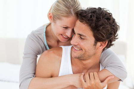 hugging couple: Lovely couple hugging on their bed at home Stock Photo