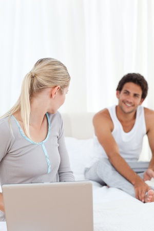 Woman talking with her boyfriend on the bed at home photo