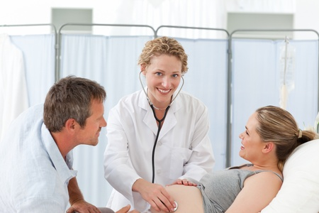 Pregnant woman with her husband and the nurse looking at the camera photo