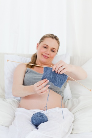 Adorable pregnant woman knitting on her bed at home photo