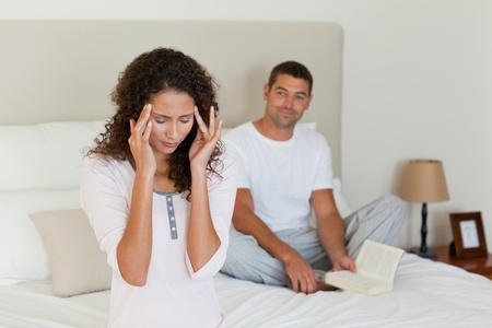 Woman having a headache while her husband is reading Stock Photo - 10172474