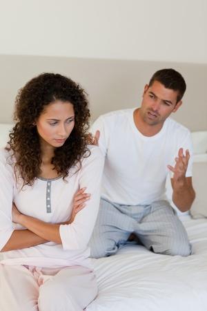 Joven pareja tener una disputa sobre la cama en su casa Foto de archivo