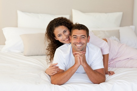 Pretty woman hugging her husband on their bed at home photo