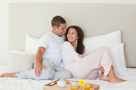 in pajama: Couple having breakfast in their bed at home Stock Photo