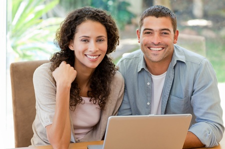 debts: Young couple calculating their domestic bills at home