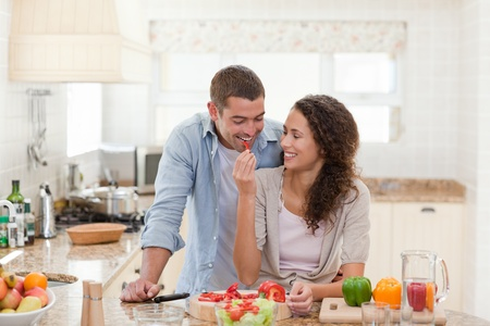 woman cooking: Handsome man cooking with his girlfriend at home