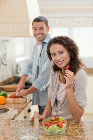 Woman eating while her husband is cooking at home Stock Photo - 10172446