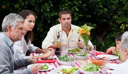 Happy family eating in the garden photo