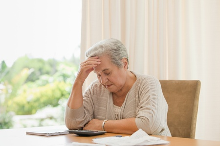 Retired woman calculating her domestic bills photo