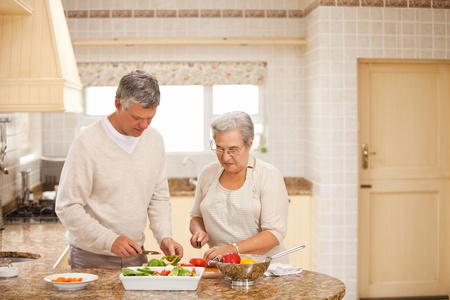 Senior couple cooking in the kitchen photo