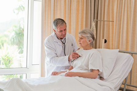 Senior doctor taking the heartbeat of his patient Stock Photo - 10173409