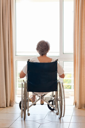 Wheel chair: Mature woman in her wheelchair with her back to the camera