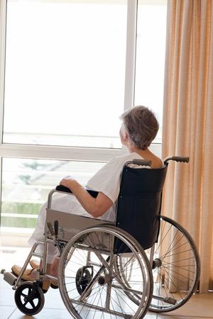 disability insurance: Senior donna in sedia a rotelle a guardare fuori dalla finestra