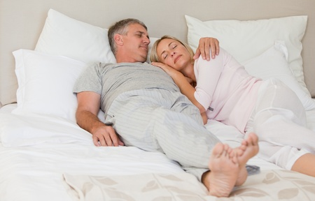 Beautiful couple sleeping on their bed Stock Photo - 10171776