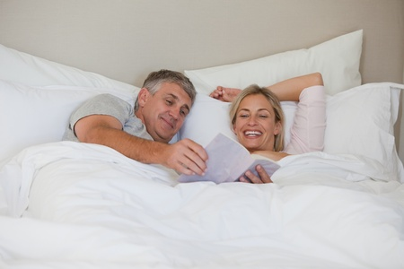Couple reading a book in their bed photo