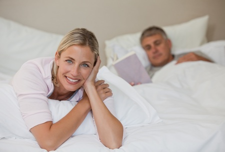 Pretty woman looking at the camera while her husband is sleeping Stock Photo - 10173556