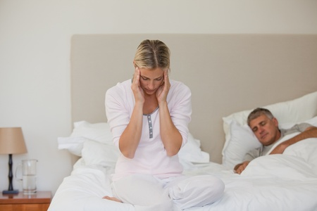 Woman having a headache while her husband is sleeping Stock Photo - 10172183