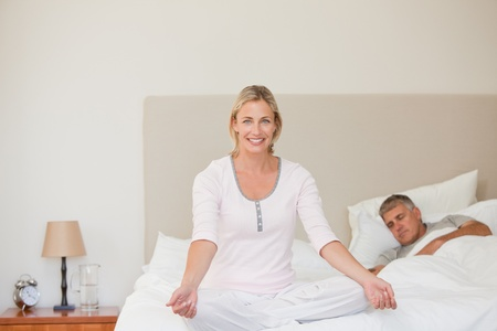Lovely woman practicing yoga on her bed photo