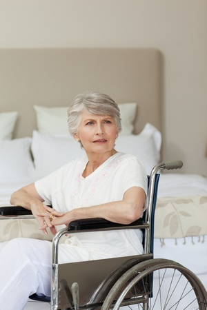 amputation: Concentrated senior woman in her wheelchair at home Stock Photo