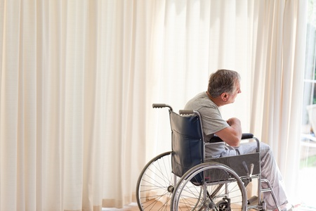 Man in his wheelchair looking out the window photo