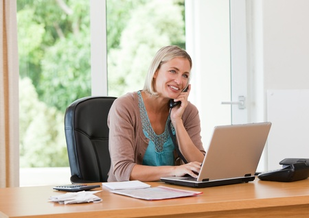 animated adult: Woman working on her computer while she is phoning