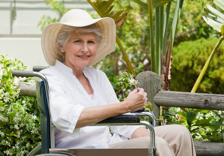 Mature woman in her wheelchair in the garden photo
