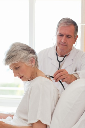 Senior doctor taking the heartbeat of his patient Stock Photo - 10173795