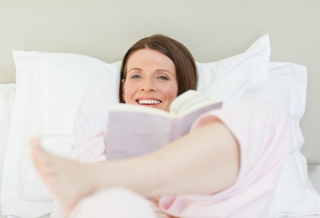 Woman reading a book on her bed Stock Photo - 10164220