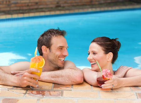 bikini pool: Beautiful couple drinking cocktails in the swimming pool