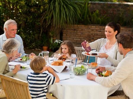 una familia comiendo: Adorable familia comiendo en el jard�n Foto de archivo