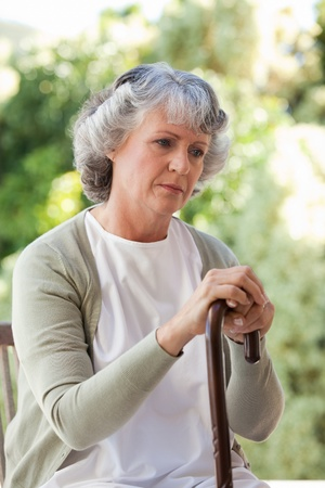 one senior adult woman: La mujer se retir� con su bast�n Foto de archivo