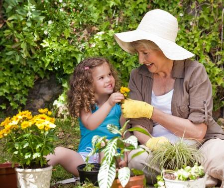 regando plantas: Abuela feliz con su nieta en el jardín Foto de archivo