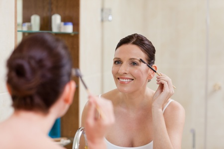 Woman curling her eyelashes photo