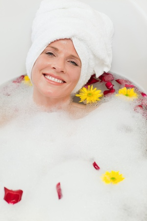Pretty woman taking a relaxing bath with a towel on her head  Stock Photo - 10172507