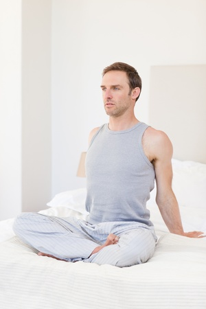 Man practicing yoga on his bed Stock Photo - 10171270