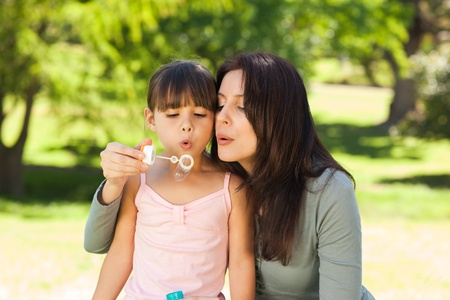 blowing bubbles: Girl blowing bubbles with her mother in the park Stock Photo