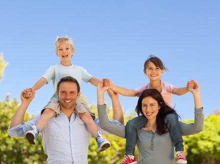 backyard woman: Parents giving  children a piggyback
