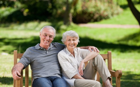 people laughing: Senior couple sitting on a bench Stock Photo