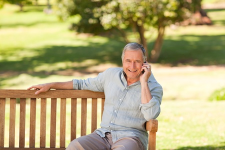 edad media: Hombre jubilado llamando telef�nicamente en el Parque Foto de archivo