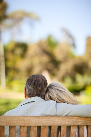 Elderly couple sitting on the bench with their back to the camera photo
