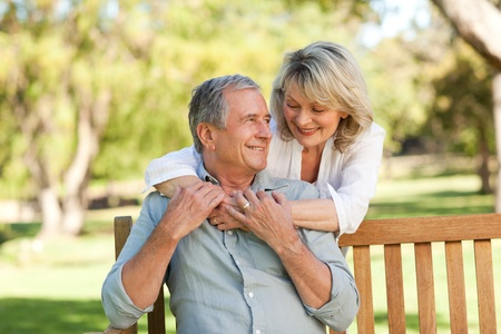human age: Senior woman hugging her husband who is on the bench Stock Photo