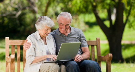 sitting on bench: Elderly couple looking at their laptop