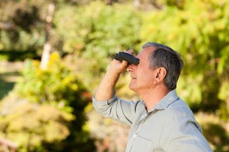 admiring: Elderly man looking at the sky with his binoculars