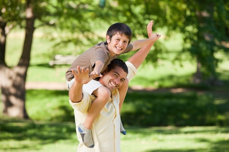 healthy people: Handsome man giving son a piggyback